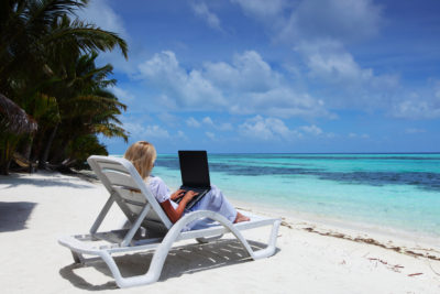 business woman with laptop lying on a chaise lounge in the tropical ocean coast